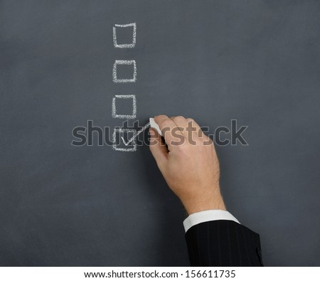tick in the box on a chalk board - stock photo