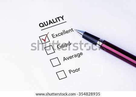 Tick placed in excellent check box on quality service satisfaction survey form with a pen on isolated white background. Business concept survey. - stock photo