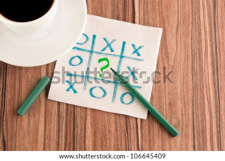 Tick-tack-toe and question mark on a napkin and cup of coffee - stock photo