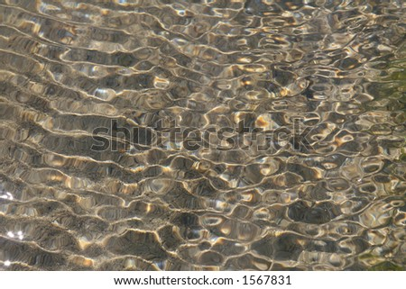 Tidal rock pools with rippling water sunlight and shadows reflections