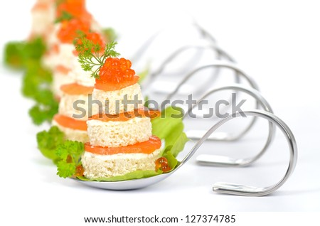 Tidbits with smoked salmon, caviar, cream cheese and toast on party spoons - stock photo