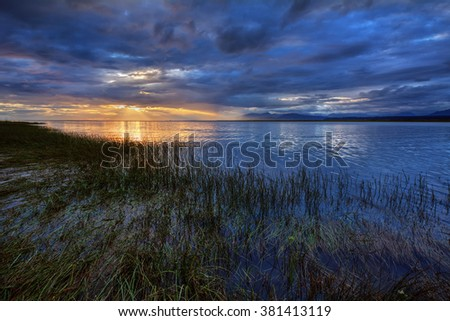Tide coming in, submerged grass, sun peeking through the dense, gray clouds - stock photo