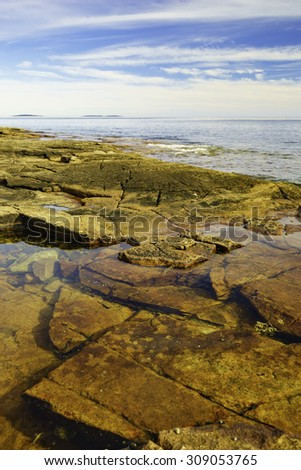 Tide pools with submerged granite slabs in Acadia National Park, Maine, and two or three islands on the horizon (shallow depth of field)