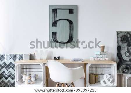 Tidy hipster stylish office with wooden desk and picture on wall - stock photo