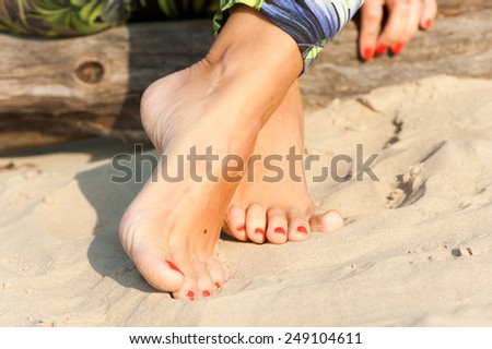 Tidy tanned sexual soft woman feet on the beach sand. Summertime outdoors close-up. - stock photo