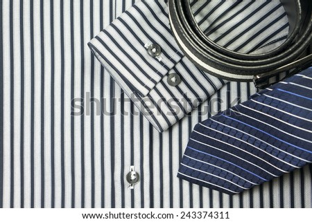 Tie and belt on striped shirt background - stock photo