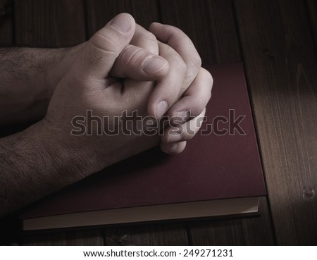 tie palms with cross fingers closeup on the Bible during prayer - stock photo
