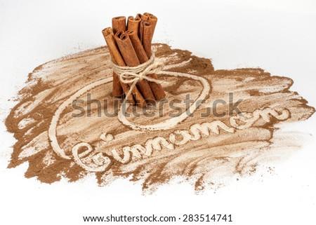 "Tied bunch of cinnamon sticks and ""Cinnamon"" hand drawn in cinnamon powder on white background - stock photo"