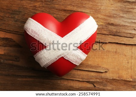 Tied heart with bandage on rustic wooden table background - stock photo