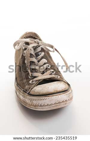 Tied old dirty sneaker standing on white surface - stock photo