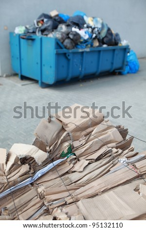 tied,segregated cardboard at the front and waste containers with nonsorted wasted in bags at the back - out of focus - stock photo