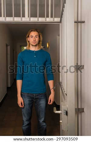 Tied to the office - Young handsome casual business guy  is strapped to metal office doors with handcuffs - looking helpless - stock photo