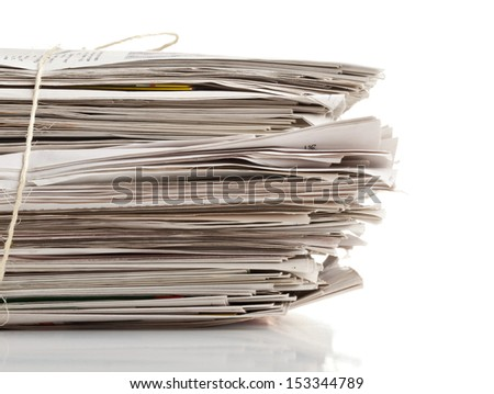 Tied up stack of old newspapers collected for recycling on white background - stock photo