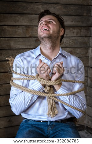 Tied With A Rope Businessman Sitting On A Chair  - stock photo