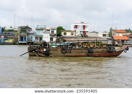 Tien Giang, Vietnam - Nov 28, 2014: Boat filled with fruits, vegetables and other products on sale on Cai Be floating market on Tien river, border between Tien Giang, Vinh Long and Ben Tre Provinces - stock photo