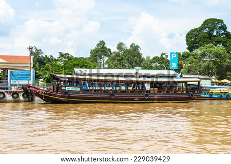 TIEN GIANG, VIETNAM - OCT 5, 2014: Wooden boat on the Mekong river in Southern Vietnam. Mekong is the 12th-longest river and flows trough China, Burma, Laos, Thailand, Cambodia, Vietnam