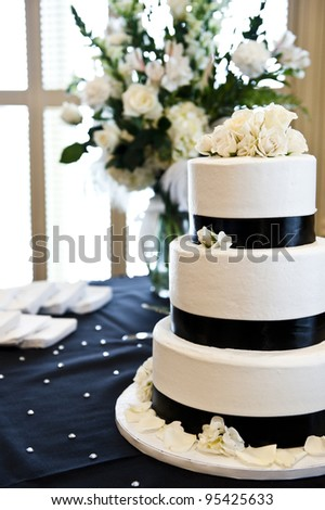 tiered wedding cake with roses on top - stock photo
