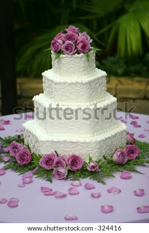 Tiered wedding cake with white frosting and purple flowers - stock photo