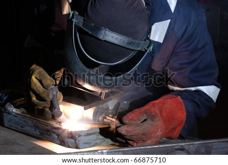 TIG welder uses torch to make sparks during manufacture of metal equipment. - stock photo
