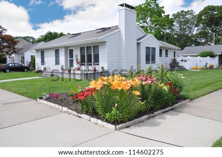 Tiger Lily Flower Garden on front yard property of suburban ranch style home in residential neighborhood - stock photo