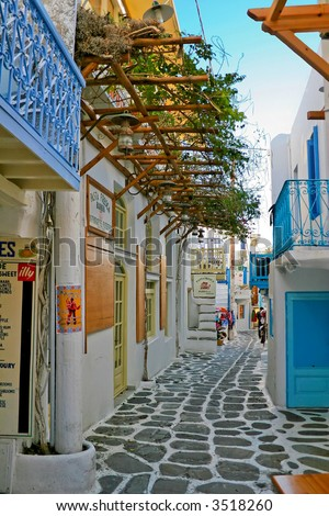 tight alley way of mykonos detailing the white wash walls and blue trim - stock photo