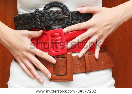Tight belts around the waist (can be used for fashion, health or budget/finance control concepts) - stock photo