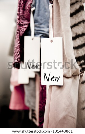 """tight crop of clothes in a boutique with a tag reading """"new"""" - stock photo"""