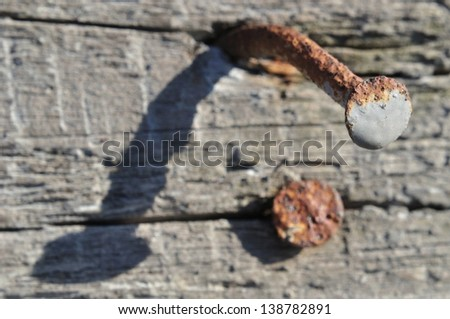 Tight focus on the head of a rusty nail in an old piece of wood - stock photo