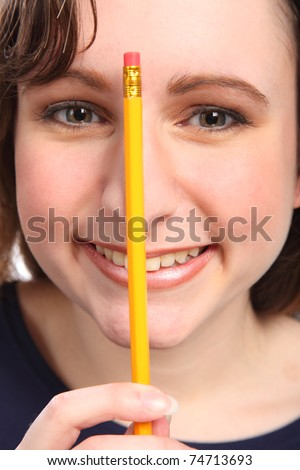 Tight headshot of young caucasian girl having fun with a pencil holding against her nose. - stock photo
