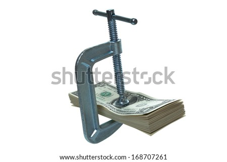 Tight on cash, c-clamp on a stack of dollar bills  - stock photo
