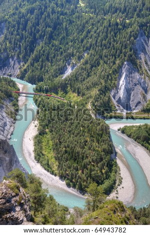 tight river bend filled with light blue water of Rhine Canyon in Switzerland seen from Flims and train Glacier Express crossing Rhine bridge - stock photo
