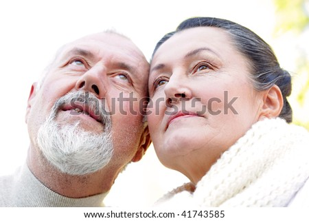 Tight shot of a content older couple looking up and away