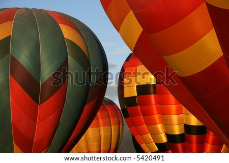 Tight shot of colorful hot air balloons getting ready for a early morning ascend - stock photo