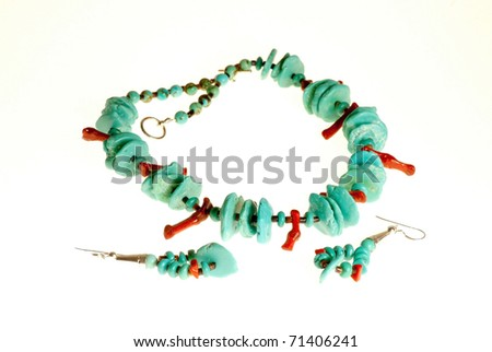 Tight shot of handcrafted Native American Turquoise and coral Jewelry isolated on white background.