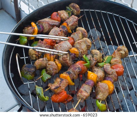 Tight shot of roasted beef kabobs with colored peppers on the BBQ kettle grill.  Juicy and delicious looking; ready to eat.