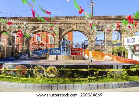 TIJUANA, MEXICO - FEBRUARY 26 2014: Plaza Santa Cecilia, a historic and traditional mexican square,with mariachi and people playing music.The concert platform, the arched wall and the saint portrayed. - stock photo