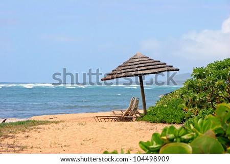 Tiki Beach Umbrella and Lounge Chairs; Tropical Kauai Hawaii - stock photo