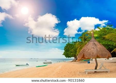 Tiki Hut on the beach with sun beds - stock photo