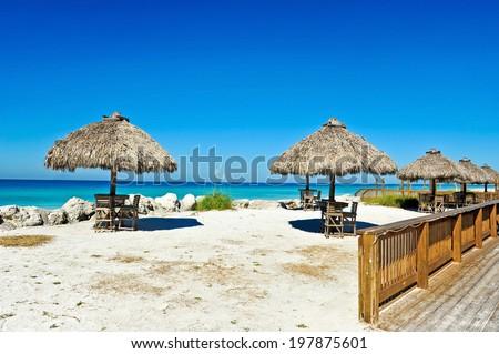 Tiki Huts at an Outdoor Bar on the Beach - stock photo