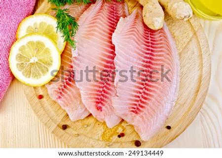 Tilapia fillets, dill, lemon, ginger, napkin on a wooden boards background - stock photo