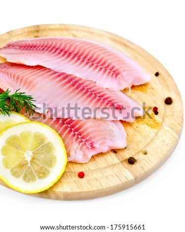 Tilapia fillets with dill, lemon slices, peppercorns on a wooden board isolated on white background - stock photo
