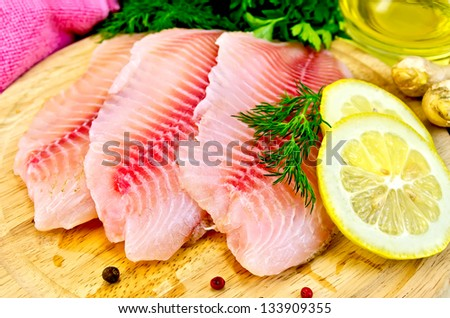 Tilapia fillets with dill, parsley, lemon, a bottle of vegetable oil, ginger, pink cloth, bell pepper on a wooden board - stock photo