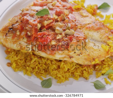 Tilapia Fillets with Yellow Rice and Vegetables - stock photo