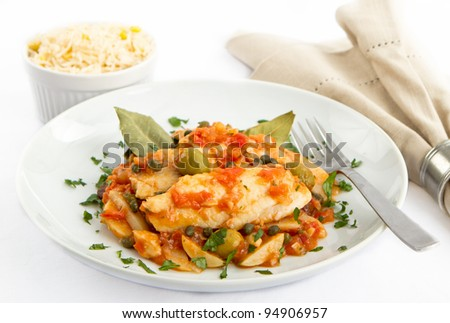 Tilapia fish prepared Veracruz style with tomatoes, potatoes, capers and olives - stock photo