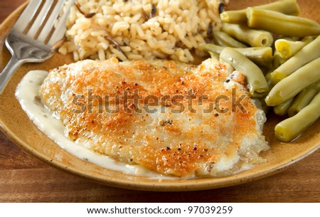 tilapia with parmesan sauce, rice and green beans - stock photo