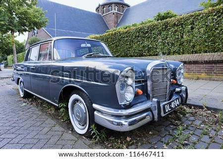 TILBURG-HOLLAND-JULY 1, 2011. Mercedes 'Fintail' in a quiet street on July 1, 2011 in Tilburg.  The Mercedes Benz 'Fintail' (W111) was a top-range four-door sedan, produced from 1959 to 1968. - stock photo