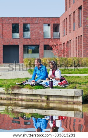 TILBURG-HOLLAND-OCT. 4, 2015. Couple enjoy sunny autumn day on canal side. October was a month of extremes in Holland, with a striking variety of sunny and gloomy periods of mild days and cold nights. - stock photo