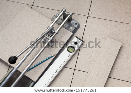 Tile-cutter, level and tiles on floor - stock photo