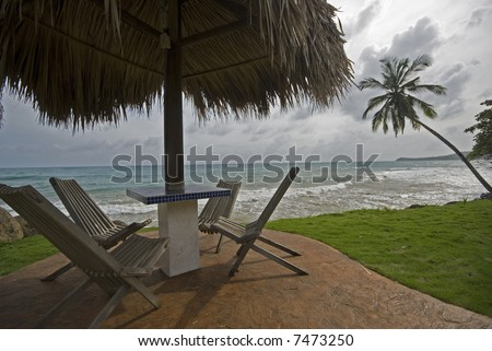 tile table with thatched roof cover by the sea resort corn island nicaragua