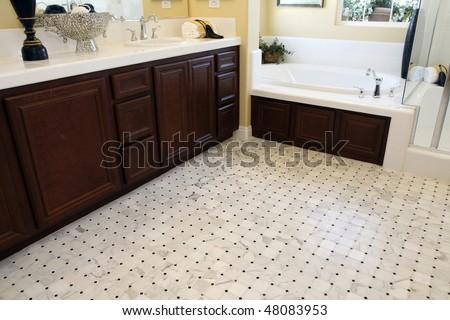 Tiled bathroom floor with a modern tub. - stock photo
